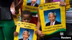 Seorang anak laki-laki memegang poster mantan presiden Afrika Selatan dekat Qunu, 13 Desember 2013.