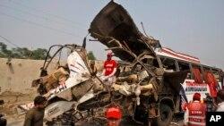Para pekerja Pakistan memeriksa bus pegawai pemerintah yang hancur akibat ledakan bom di Peshawar, Pakistan (27/9).