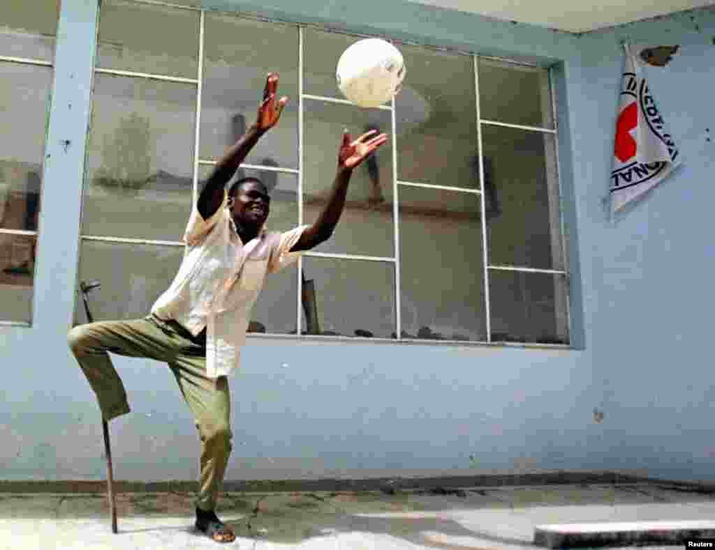 Soldado ferido joga bola no centro ortopédico de Huambo em fevereiro de 1998