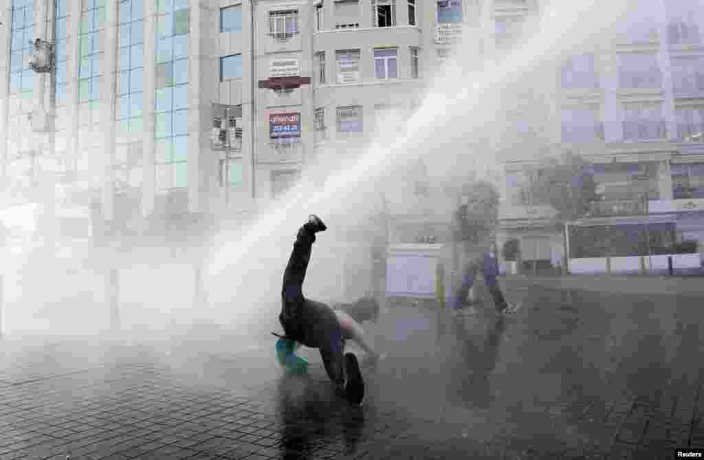 A demonstrator falls after being hit by water cannon used by riot police to disperse the crowd during a protest against the destruction of trees in a park brought about by a pedestrian project, in Taksim Square in central Istanbul.
