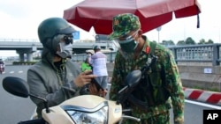 An army soldier checks identifications at a COVID-19 lockdown checkpoint in Ho Chi Minh City, Vietnam, Monday, Aug. 23, 2021. (Vu Tien Luc/VNA via AP)