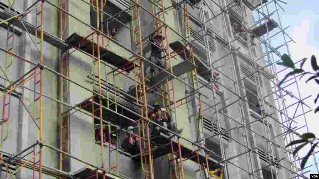 Construction workers on scaffolding ceased their work to watch opposition protest and take pictures, Phnom Penh, Oct. 23, 2013. (Khoun Theara/VOA Khmer)