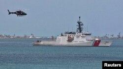 Un helicóptero vuela cerca de un barco de la Guardia Costera estadounidense en el Puerto de San Juan, Puerto Rico.