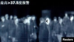 Temperatures of travelers are monitored by thermal scanner to fevers and other symptoms at train station in Beijing, file photo.