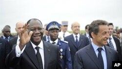 Le président Alassane Ouattara (à g.) en compagnie de son homologue français Nicolas Sarkozy, samedi à l'aéroport de Yamoussoukro.
