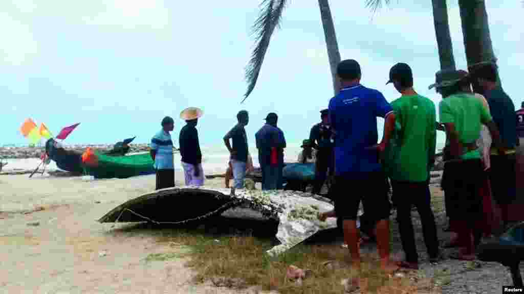 People stand next to a piece of suspected plane wreckage which has been found off the coast of southern Thailand in Nakhon Si Thammarat province, Jan. 24, 2016.