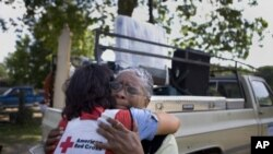 Joann Parks hugs Janice Sawyer as the Mississippi River's flooding waters rapidly near her home in Vicksburg.