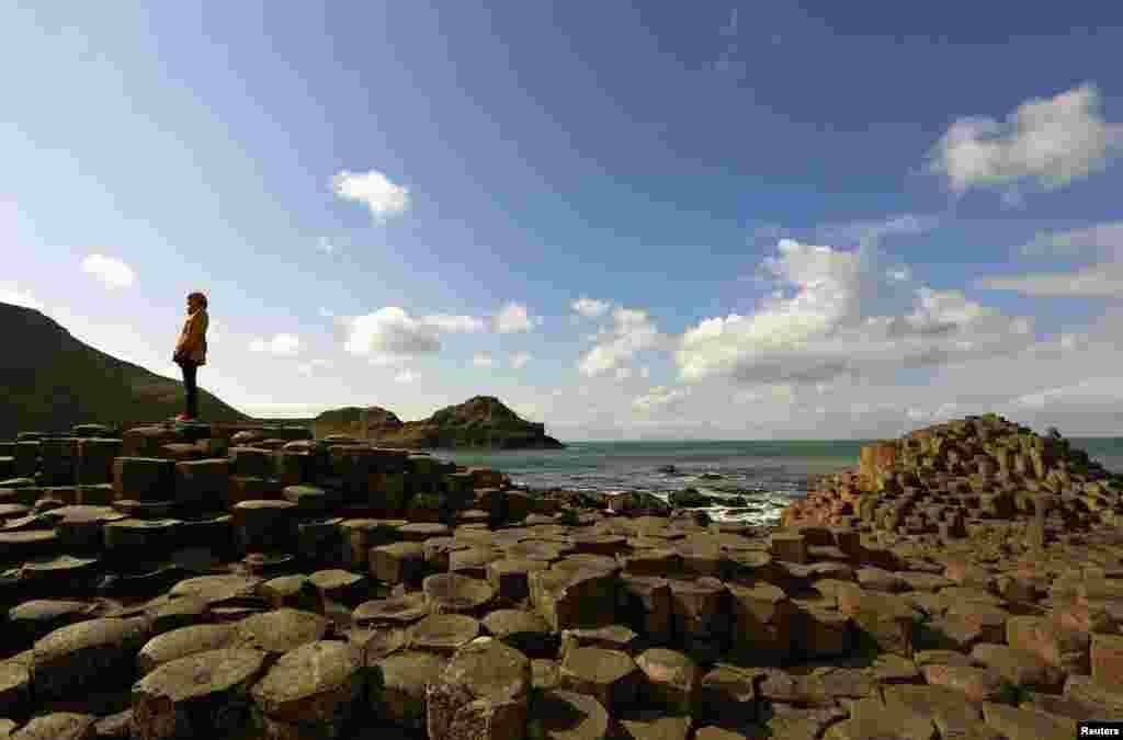"""Seorang perempuan berdiri pada batu-batu karang """"Giant's Causeway"""" di Irlandia Utara."""