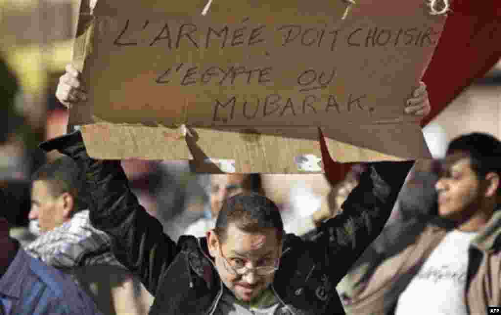 """An anti-government protester holds a banner in French referring to the Egyptian President and reading """"The army must choose Egypt or Mubarak"""", at the continuing demonstration in Tahrir square in downtown Cairo, Egypt, Monday, Jan. 31, 2011. A coalition of"""