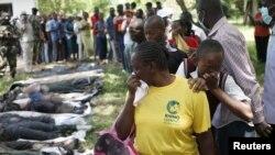 Quelques personnes réagissent devant des corps des combattants d'al Shebab tués dans des combats contre l'armée, en Mpekatoni, au Kenya, 15 juin 2015. REUTERS / Goran Tomasevic