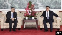 This Macau Government handout picture released on December 19, 2014 shows Chinese President Xi Jinping (R) meeting with Macau Chief Executive Fernando Chui at the San Chok Un Guesthouse in Macau, Dec. 19, 2014.