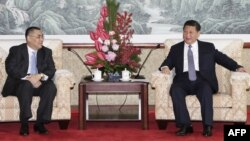 A Macau government handout picture shows Chinese President Xi Jinping (R) meeting with Macau Chief Executive Fernando Chui at the San Chok Un Guesthouse in Macau, Dec. 19, 2014.