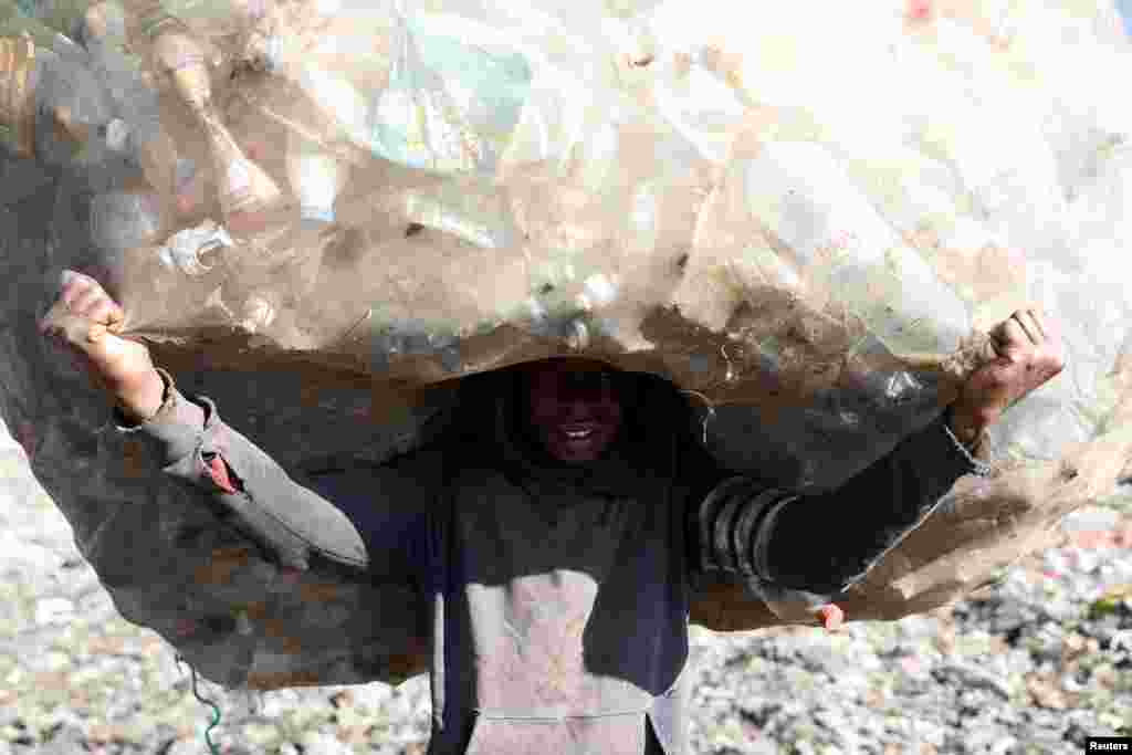 A man carries a sack full of plastic bottles in the Andralanitra garbage dump in Antananarivo, Madagascar.