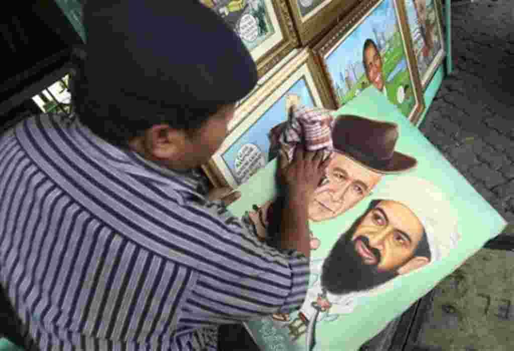 El pintor S. Wito, de Indonesia, seca la pintura de Osama bin Laden y el ex presidente de EE.UU. George Bush en su estudio de la calle del lado en Yakarta, Indonesia.