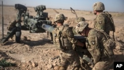 FILE - U.S. soldiers with Task Force Iron maneuver an M-777 howitzer so it can be towed into position at Bost Airfield, Afghanistan, June 10, 2017. (Operation Resolute Support)