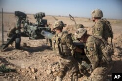 FILE - Photo provided by Operation Resolute Support, U.S. Soldiers with Task Force Iron maneuver an M-777 howitzer, so it can be towed into position at Bost Airfield, Afghanistan, June 10, 2017.