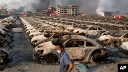 A man walks past wreckage from the Tianjin warehouse explosion.