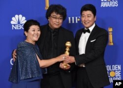 """Lee Jeong-eun, from left, director Bong Joon-ho and Kang-Ho Song, from the cast and crew of """"Parasite,"""" pose in the press room with the award for best foreign language motion picture at the 77th annual Golden Globe Awards."""