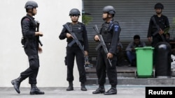 FILE - Indonesian police stand guard at the site of a militant attack in central Jakarta, Indonesia, Jan. 16, 2016. Police say six Islamic militants planned to attack police officers in East Java, but they were killed in a standoff first.