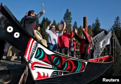FILE - Members of the First Nation Tsleil-Waututh, Squamish and Musqueam bands sing during a protest of the Trans Mountain pipeline expansion in North Vancouver, British Columbia, Oct. 14, 2013.