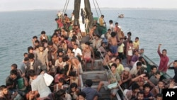 FILE - Rohingya Migrants wait to be be rescued by Acehnese fishermen on their boat on the sea off East Aceh, Indonesia, Wednesday, May 20, 2015.