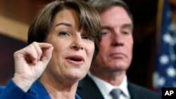 Sen. Amy Klobuchar, D-Minn., left, and Sen. Mark Warner, D-Va., speak about online political ads and preventing foreign interference in U.S. elections, during a news conference on Capitol Hill in Washington, Oct. 19, 2017.