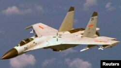 FILE - This Chinese J-11 fighter jet flew near a U.S. Navy P-8 Poseidon about 215 kilometers (135 miles) east of China's Hainan Island in this U.S. Department of Defense handout photo taken Aug. 19, 2014.