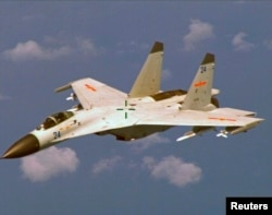 FILE - A Chinese J-11 fighter jet is seen flying near a U.S. Navy P-8 Poseidon about 215 km (135 miles) east of China's Hainan Island in this U.S. Department of Defense handout photo taken, Aug. 19, 2014.