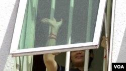 Tep Vanny melambaikan tangannya dari jendela di pengadilan Phnom Penh, 17 Agustus 2016 (Foto: VOA Khmer/Leng Len) 