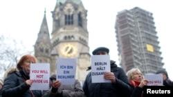 "Waga Berlin dan para pengungsi berkumpul bersama menyanyikan lagu ""We Are The World"" di depan Kaiser Wilhelm Gedaechtniskirche (Gereja untuk memperingati Kaiser Wilhelm) di Berlin, Jerman, 21 Desember 2016, pasca insiden pasar Natal yang mengguncang kota itu Senin malam."