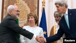 U.S. Secretary of State John Kerry, right, and Iranian Foreign Minister Javad Zarif, left, shake hands as Omani Foreign Minister Yussef bin Alawi, second from right, and EU envoy Catherine Ashton watch in Muscat, Oman, Nov. 9, 2014.
