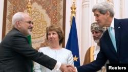 美国国务卿克里(右)和伊朗外长扎里夫(左)11月9日在阿曼握手。左二是欧盟特使阿什顿,左三是阿曼外长阿拉维。