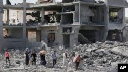 Người Palestine đi bộ trên đống đổ nát của các ngôi nhà bị phá hủy bởi cuộc phản công của Israel trước cuộc ngưng bắn, ở Beit Hanoun, phía bắc Dải Gaza, 26/7/2014.