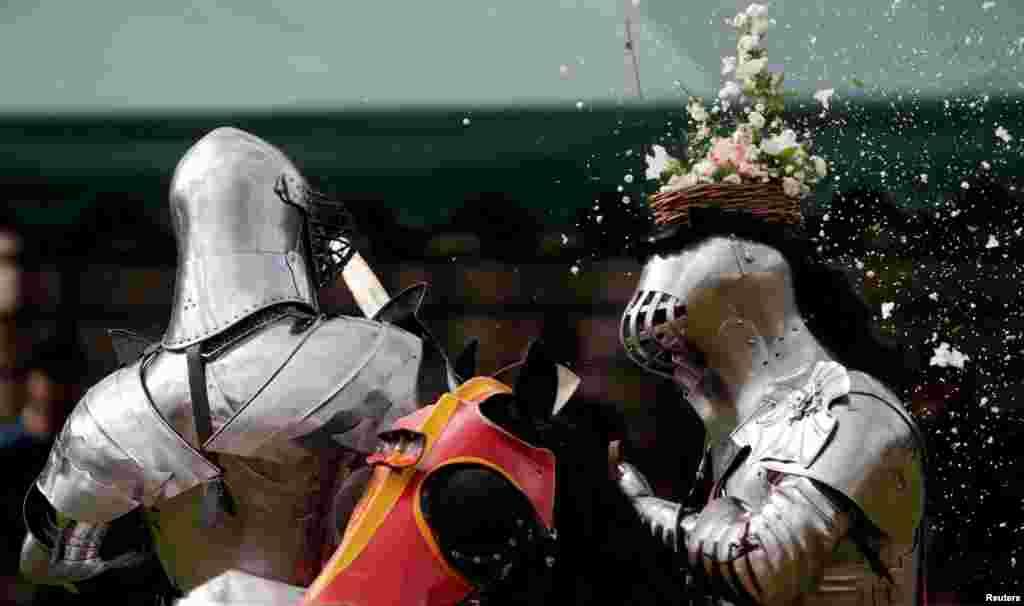 កីឡាករប្រយុទ្ធដាវ Philip Leitch (រូបឆ្វេង) របស់អូស្រា្តលីមានកន្ត្រក់ផ្កានៅលើមួកការពាររបស់គាត់ ហើយត្រូវបានកម្ទេចដោយគូប្រកួតរបស់ខ្លួន នៅក្នុងការតាំងពិព័រណ៍ St. Ives Medieval Fair ក្នុងក្រុងស៊ីដនី ប្រទេសអូស្រា្តលី។