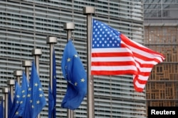 FILE - U.S. and European Union flags are pictured at European Commission headquarters in Brussels, Belgium