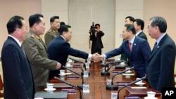 Ketua delegasi Korea Selatan Kim Kyou-hyun (dua dari kanan) berjabat tangan dengan ketua delegasi Korea Utara Won Tong Yon (tiga dari kiri) dalam pertemuan di desa perbatasan Panmunjom, Korea Selatan (12/2).
