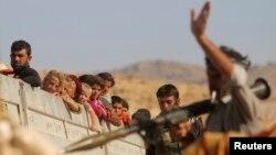 13일 이라크 북부 신자르 산 난민들이 쿠르드족 군대의 호위를 받으며 시리아 난민촌으로 떠나고 있다.