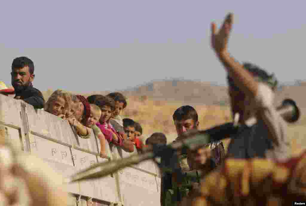 A Yazidi fighter who recently joined the Kurdish People's Protection Units (YPG) gestures while securing a road in Mount Sinjar, northern Iraq, for displaced Yazidi refugees, Aug. 13, 2014.