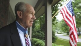 In this Friday, July 12, 2013 photo, retired U.S. Navy Capt. Thomas Hudner, who was awarded the Medal of Honor by President Truman, poses on the porch at his home in Concord, Mass.
