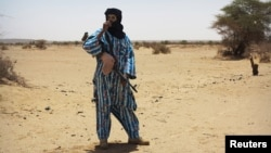 FILE - A fighter with the Tuareg separatist group MNLA stands guard outside the local regional assembly in Kidal, Mali, June 23, 2013.
