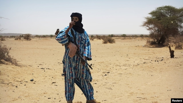 A fighter with the Tuareg separatist group MNLA stands guard outside the local regional assembly in Kidal, Mali, June 23, 2013.
