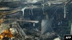 Nhân viên cứu hỏa Trung Quốc xem xét hiện trường sau vụ nổ tại quán cà phê Internet ở tỉnh Quý Châu, ngày 5/12/2010