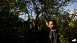 ၂၀၁၃ ခုႏွစ္က တပ္ေျပး ကေလးစစ္သားတဦး သူ ရက္ေပါင္းမ်ားစြာ ပုန္းေအာင္းခဲ့ရာ သစ္ပင္မ်ားကို ျပန္လည္ျပသေနစဥ္။