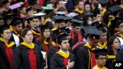 FILE - New graduates participate in a Rutgers University graduation ceremony in Piscataway Township, N.J., Sunday, May 13, 2018. (AP Photo/Seth Wenig)