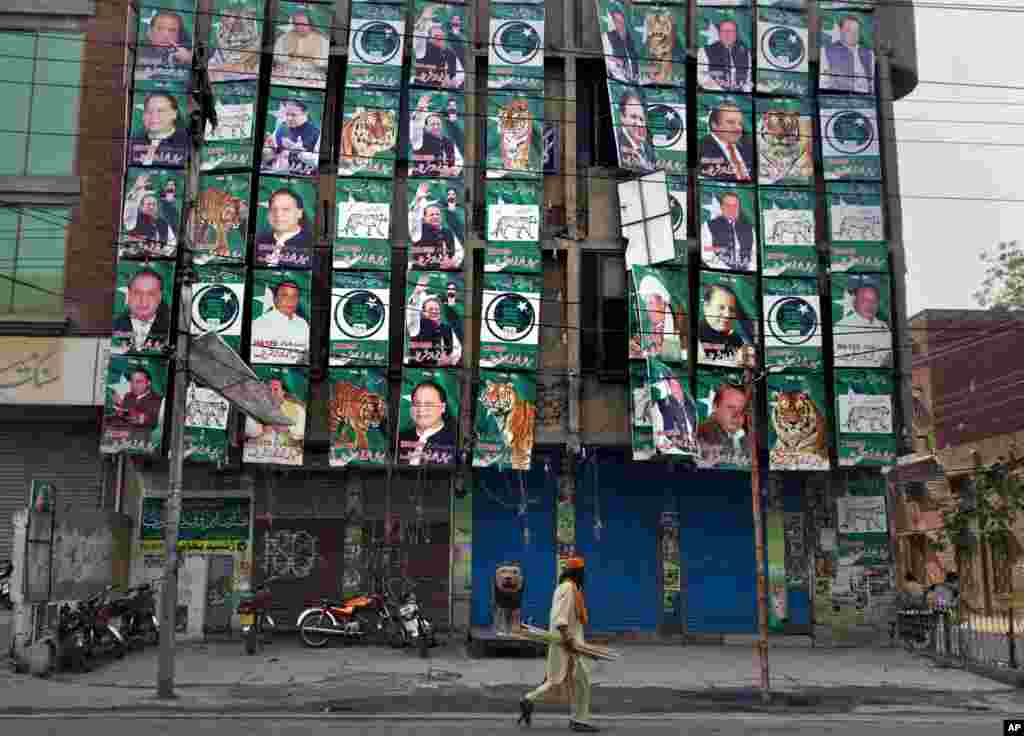 A man walks past posters of former prime minister and Pakistan Muslim League party chief Nawaz Sharif, displayed on his party's office building in Lahore, May 12, 2013.