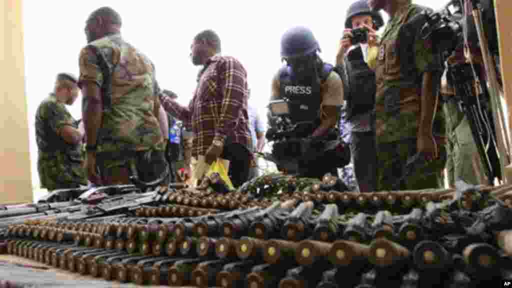 Journalists look at arms and ammunition which military commanders say they previously seized from Islamic fighters in Maiduguri, Nigeria.