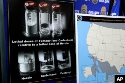 Posters comparing lethal amounts of heroin, fentanyl and carfentanil are on display during a news conference about the dangers of fentanyl at DEA Headquarters in Arlington, Va., June 6, 2017.