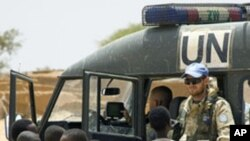 A United Nations Mission in the Central African Republic and Chad (MINURCAT) peacekeeper is seen with Sudanese children from the Oure Cassoni refugee camp in Bahaï, Eastern Chad, 16 Oct 2009