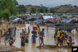 Rohingya Muslims, who crossed over from Myanmar into Bangladesh, carry their children and belongings after their camp was inundated with rainwater near Balukhali refugee camp, Bangladesh, Sept. 19, 2017.