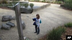 FILE - A tourist reads names on a memorial at Port Arthur, Tasmania state, Australia.
